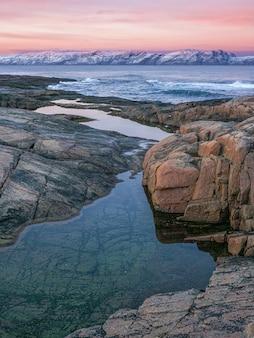 북극 흰색 눈 덮인 산맥의 놀라운 일출 풍경. 바 렌츠 해의 해안에 협곡과 케이프가있는 멋진 산 풍경.