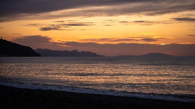 熱帯のビーチの素晴らしい日の出海の上の黄色い太陽自然の背景