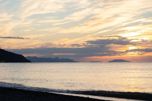 熱帯のビーチからの素晴らしい日の出。海の上の黄色い太陽。オレンジ色の波。自然の背景。美しい穏やかなシーン。朝。日光は水面に反射します
