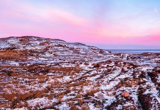 ロッキー山脈の背後にある山々の白い雪の尾根と崖のある素晴らしい日の出の極地の風景。バレンツ海のツンドラと素晴らしいパノラマの山の風景。