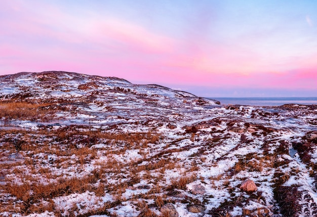 Amazing sunrise polar landscape with a white snow ridge of mountains behind the rocky mountains and a cliff. wonderful panoramic mountain landscape with tundra on the barents sea.