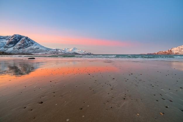 Удивительный восход солнца с удивительным пурпурным цветом над песчаным пляжем