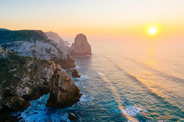 ポルトガルの大西洋のすばらしい夕日。ケープロックファンタジーシースケープ。夕方には岩と山のあるカラフルな風光明媚な海の大きな高さからの眺め。熱帯の楽園。