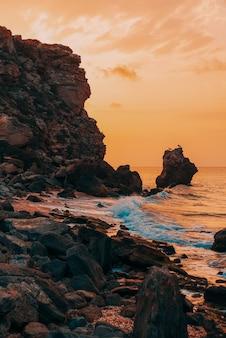 바다의 놀라운 일몰, 자연의 아름다움. 바다, 바위가 많은 해안선과 모래 해변, 황금빛 하늘과 태양의 아름다운 전망. 환상적인 하늘에 공간을 복사합니다. 세로 촬영.