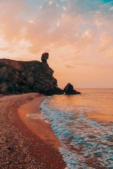 Изумительный закат на море, красота природы. живописный вид на море, скалистую береговую линию и песчаный пляж, золотое небо и солнце. скопируйте пространство на фантастическом небе. вертикальный побег.