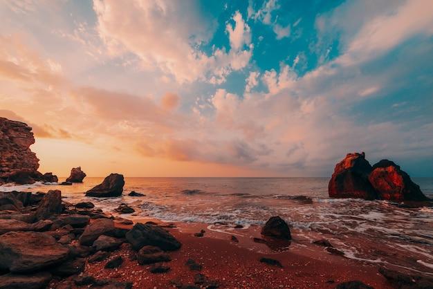 바다의 놀라운 일몰, 자연의 아름다움. 바다, 바위가 많은 해안선과 모래 해변, 황금빛 하늘과 태양, 야외 여행 배경의 아름다운 전망. 장군의 해변. 크림.