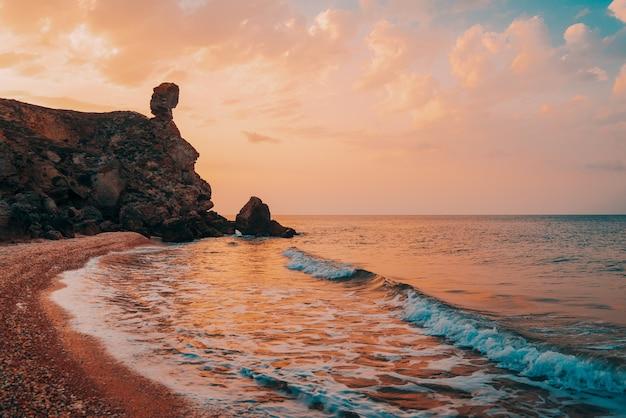 Изумительный закат на море, красота природы. живописный вид на море, скалистую береговую линию и песчаный пляж, золотое небо и солнце, открытый фон путешествия. генеральские пляжи. крым.