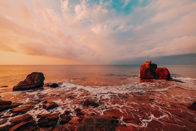 Изумительный закат на море, красота природы. живописный вид на море, скалистое побережье и песчаный пляж, золотое небо и солнце