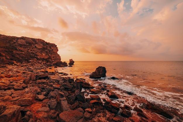 바다의 놀라운 일몰, 자연의 아름다움. 바다, 바위가 많은 해안선과 모래 해변, 황금빛 하늘과 태양의 아름다운 전망