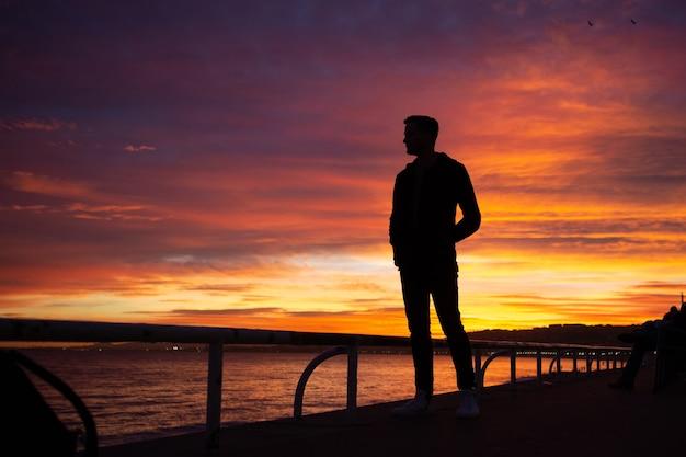 Удивительный закат в ницце. силуэт человека, стоящего на берегу