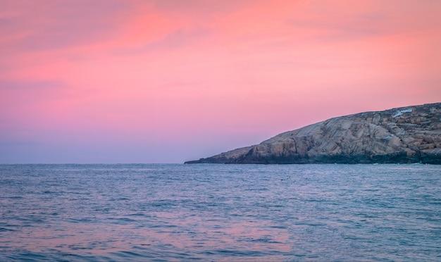 地平線に山脈がある素晴らしい夕日の極地の風景。北極海のパノラマビュー。コラ半島。