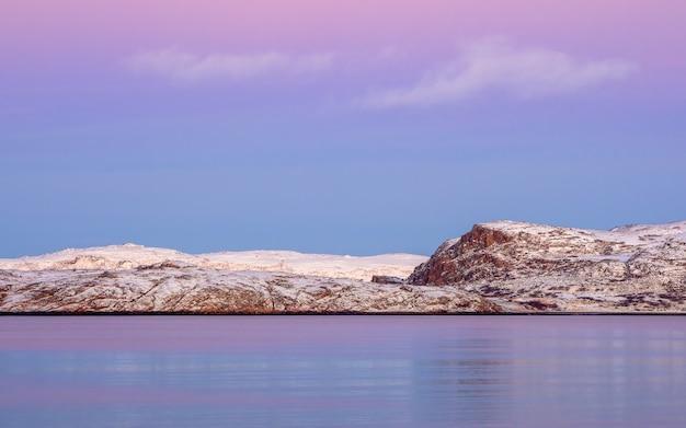 地平線上に白い雪に覆われた山脈と素晴らしい夕日の極地の風景。北極海のパノラマビュー。