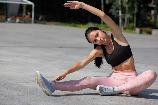 Amazing tanned athletic girl wearing sport apparel doing stretching workout at the park. space for text