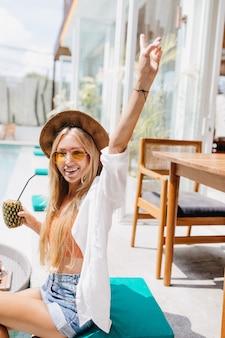 Incredibile donna abbronzata con acconciatura lunga in posa al resort con cocktail di ananas. bella donna bionda in occhiali da sole e camicia bianca divertendosi nel fine settimana estivo.