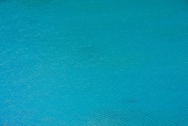 Amazing textured background of calm azure clean water surface.