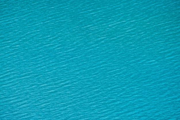 Удивительный текстурированный фон спокойной лазурной поверхности чистой воды. солнечный свет в горном озере заделывают.