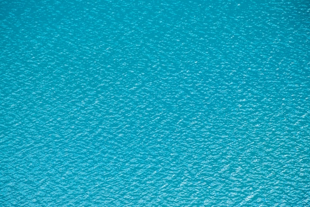 Amazing textured  calm azure clean water surface. sunshine in mountain lake close up. beautiful ripples on shiny water in sunny day. wonderful relax texture.