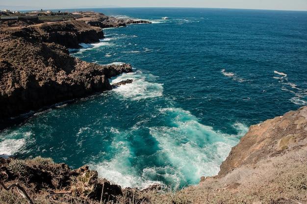 Удивительный вид сверху с горы на яркое глубокое море с волнами под чистым голубым небом в солнечный день