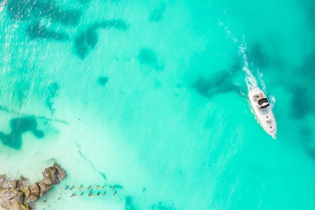 Удивительный вид сверху яхты с высоты птичьего полета роскошного плавучего небольшого корабля в голубой карибской морской яхте в
