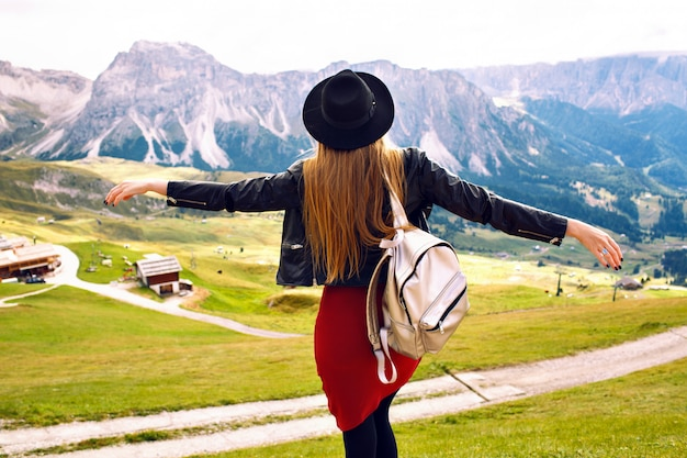 Amazing traveling experience image of beautiful stylish woman posing back and looking at breathtaking mountains view, trip in italian dolomites. hipster girl enjoying adventures.