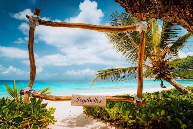 ターコイズブルーの海と白い砂浜の竹のフレームで素晴らしい熱帯のシーン。楽園での休暇。マヘ島、セイシェル。 Premium写真