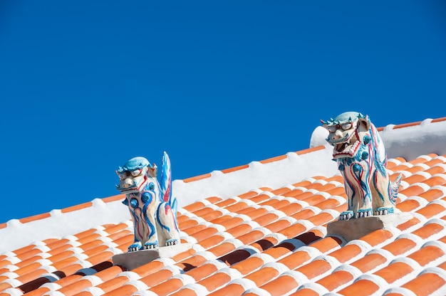 Amazing two highly colored shisa statues male and female used as protection on top of the red roof