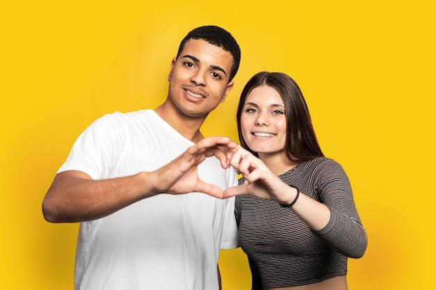 Удивительные два человека парень леди празднует день святого валентина держит пальцы в форме фигуры сердца смотрит в камеру и улыбается, одетые в повседневные футболки изолированные желтый