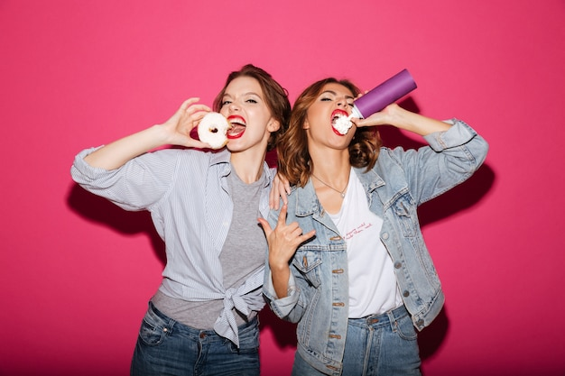 Amazing two women friends eating sweeties