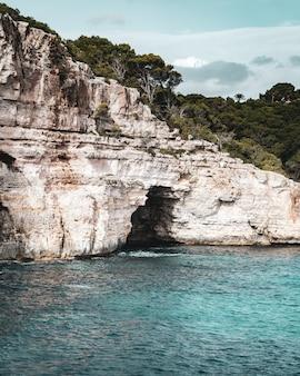 Удивительный вертикальный снимок пещеры, расположенной в огромной скале на берегу моря.