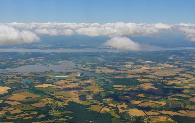 Удивительный вид самолета над кучевыми пушистыми облаками панорамный земля зеленая трава поля леса голубое небо