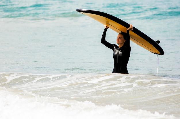 Vista spettacolare. bella ragazza sta con una tavola da surf sulla riva dell'oceano