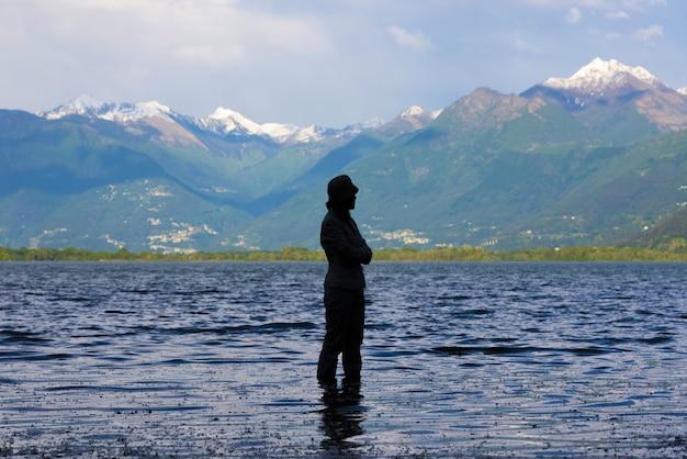 Incredibile vista di una silhouette femminile in piedi nel mezzo di un lago
