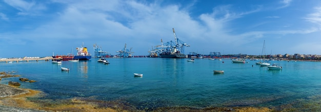 An amazing view of an industrial port with many cargo ships near construction cranes on the sea on the background of a blue sky in malta.