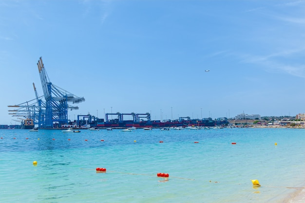 An amazing view of an industrial port with many cargo ships near construction cranes