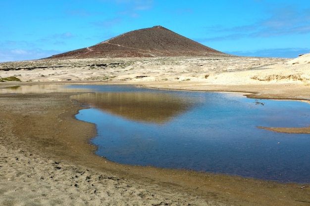 Amazing view of montana roja volcano with pond in natural reserve of sand desert of el medano, tenerife, spain
