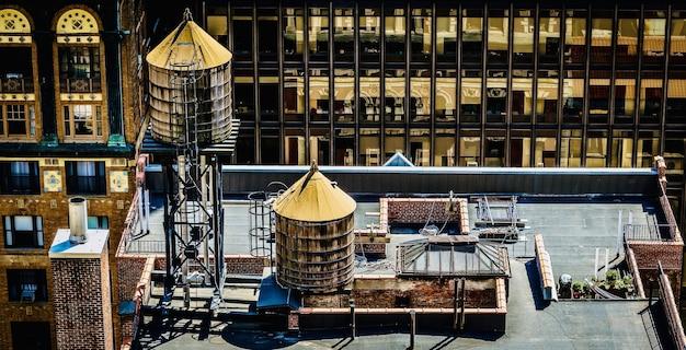 水タンクが付いているダウンタウンの建物の屋根の素晴らしい景色