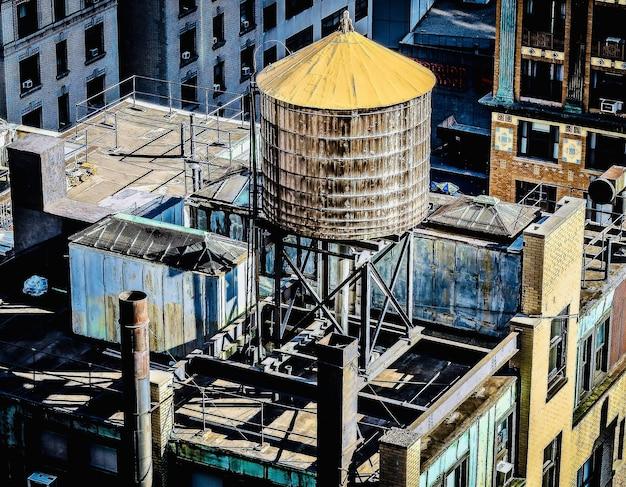 물 탱크가있는 시내 건물 지붕의 놀라운 전망