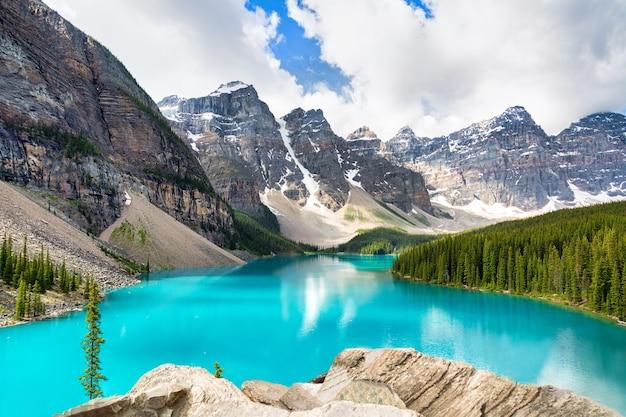 カナダのバンフにある有名なモレーン湖の素晴らしい景色国立公園のロッキー山脈を反映した澄んだ青い水