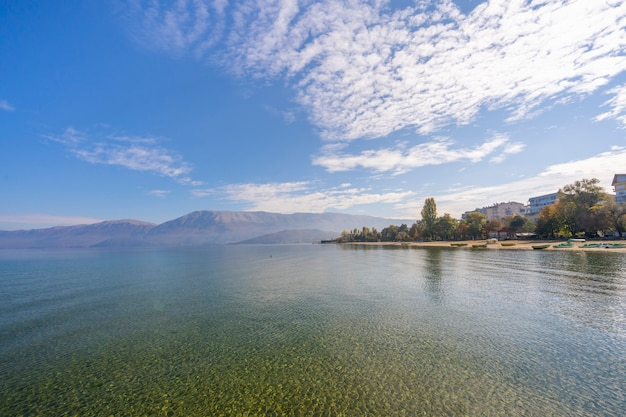 緑の木々、山々、ターコイズブルーの水と日の出のカラフルな青い空と海の素晴らしい景色