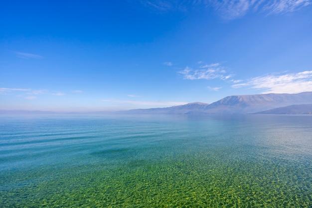 緑の木々、山々、ターコイズブルーの水と日の出のカラフルな青い空と海の素晴らしい景色 Premium写真