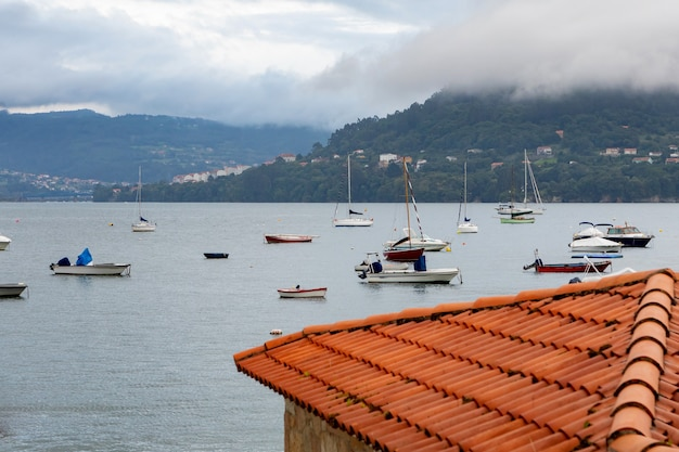 Amazing view of the sea with boats and a roof in the foreground