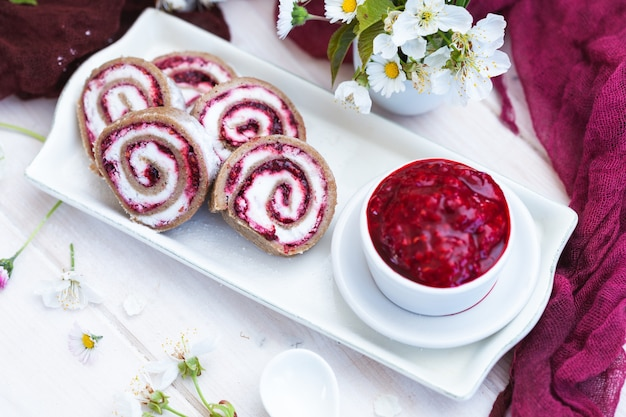 Amazing view of tasty looking raspberry rolls and raspberry jam put on a white plate