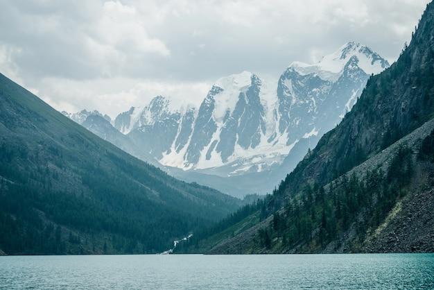 Прекрасный вид на большие заснеженные горы и горное озеро.