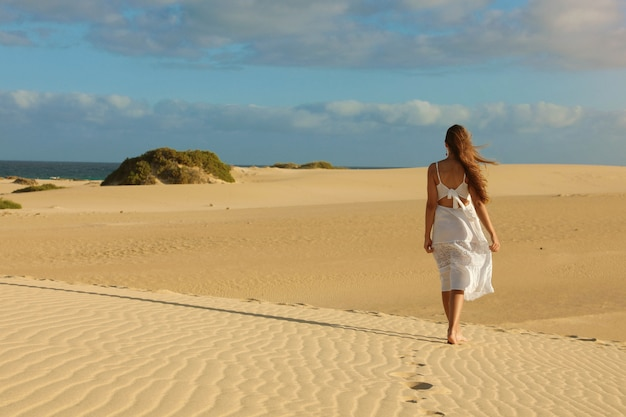 Amazing view of young woman walking barefoot on desert dunes at sunset in corralejo, fuerteventura