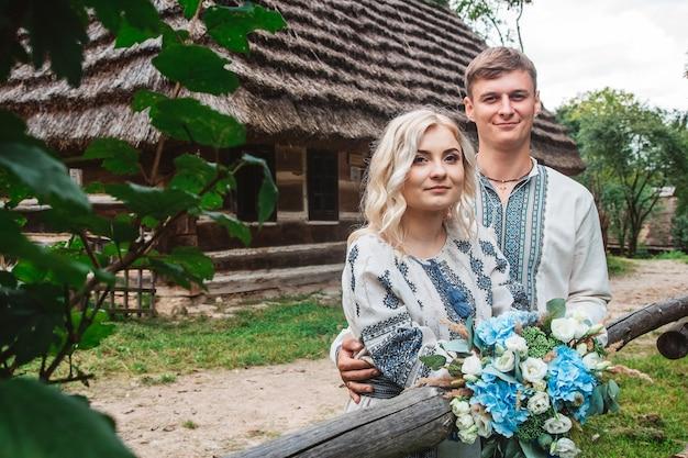 Удивительная свадебная пара, взявшись за руки и обнимаясь на фоне деревянного дома.