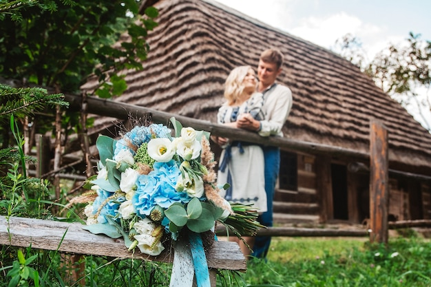 Amazing wedding couple holding hands and hugging against a background of a wooden house