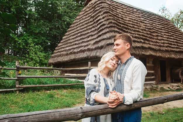 Amazing wedding couple holding hands and hugging against a background of a wooden house.
