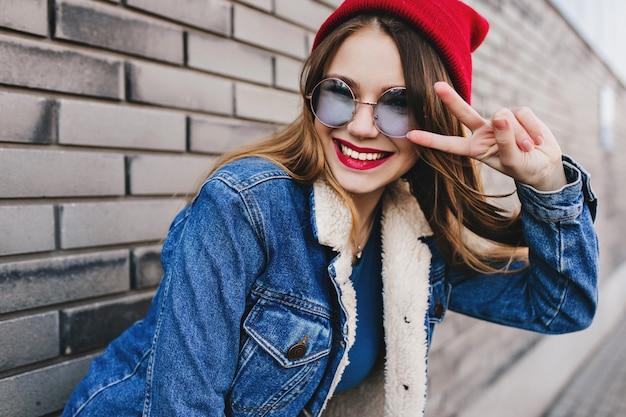 ピースサインでポーズをとる流行の丸いメガネの素晴らしい白人の女の子。ぼやけたレンガの壁で笑っている賢いブルネットの女性の屋外ショット。