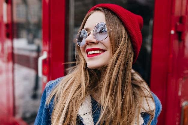 赤の電話でポーズをとってデニムジャケットの素晴らしい白人女性