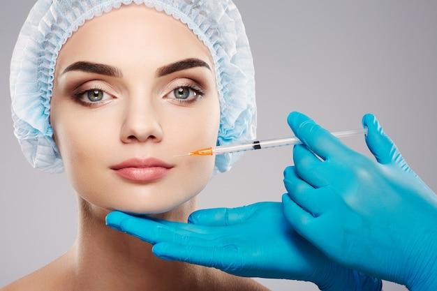 Удивительно с обнаженным макияжем на фоне студии, руки врача в синих перчатках возле лица пациента, концепция красоты, глядя в камеру, инъекция ботекса.